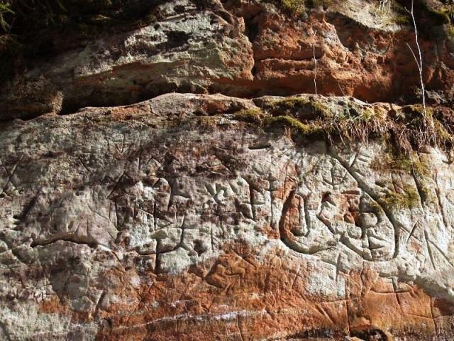 """Viena no """"zīmju klintīm"""" Ziemeļlatvijā, kur redzama arī J. Bēmes uz augšu apgrieztā sirds."""